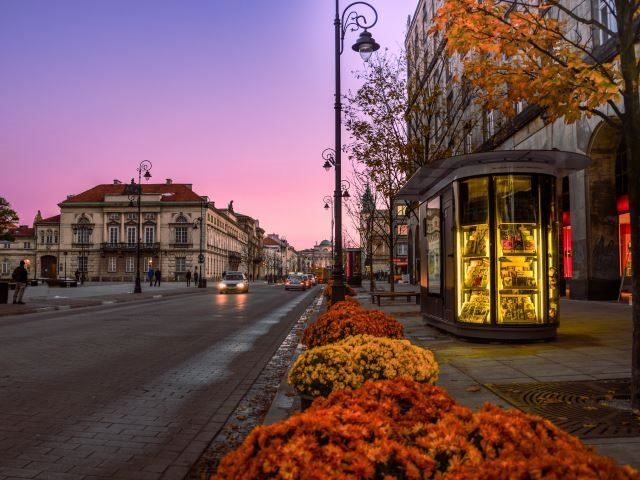A colorful sunset on an old newspaper stand with flowers and cars in the background - news concept