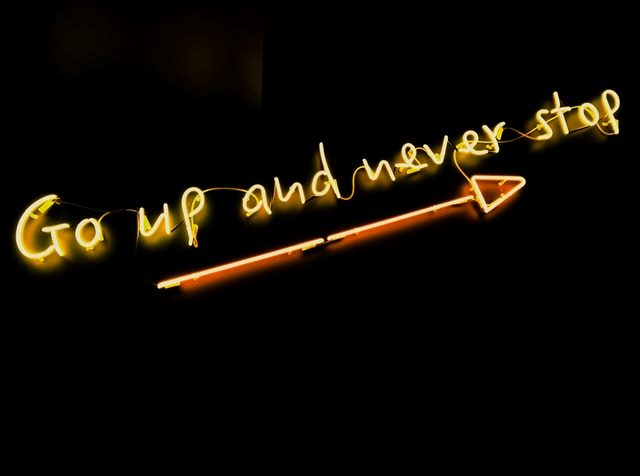 Neon message with up arrow saying go up and never stop