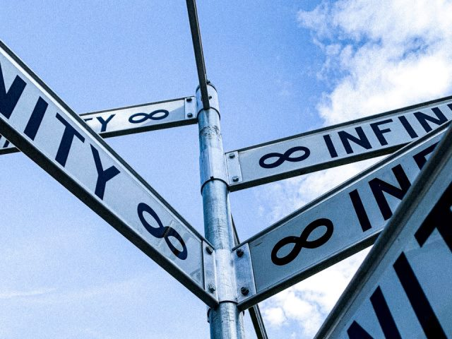 Infinity street signs against a blue sky
