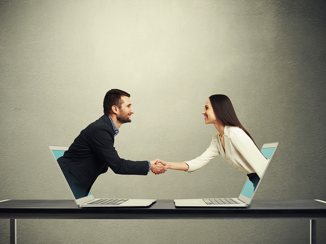 Businessman and businesswoman come out from laptop, shaking hands and looking at each other over dark grey background