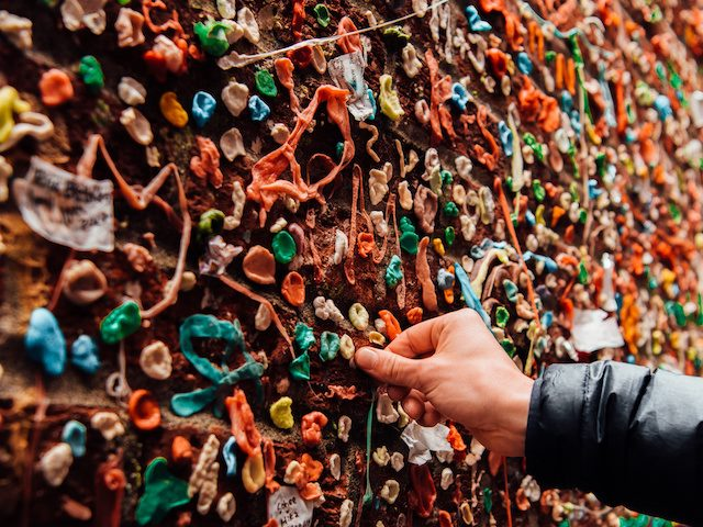person adding some gum to a wall covered in chewing gum in Portland, Oregon