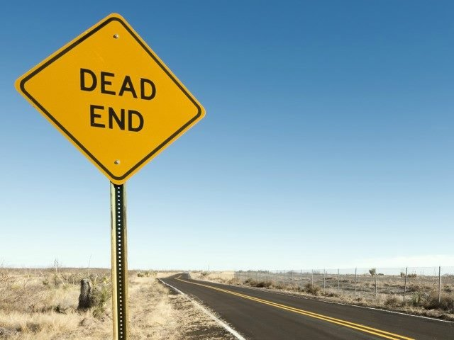 A dead-end sign on an open road.
