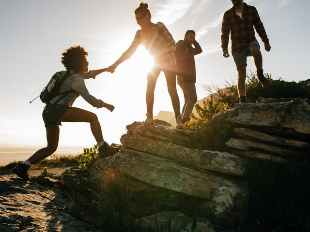 Group of hikers on a mountain, with a woman helping her friend to climb, at sunset.