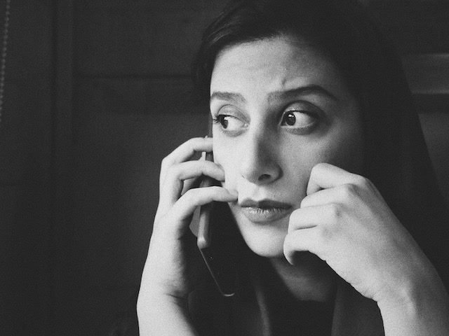 pensive  looking woman on a phone  call