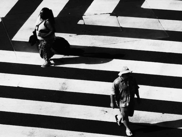 zig  zag crosswalk, people  walking  in opposite  directions