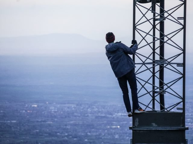 man climbing on a tower to look out in the distance