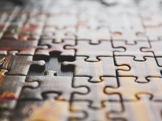 brown and black jigsaw puzzle on a table with one piece missing