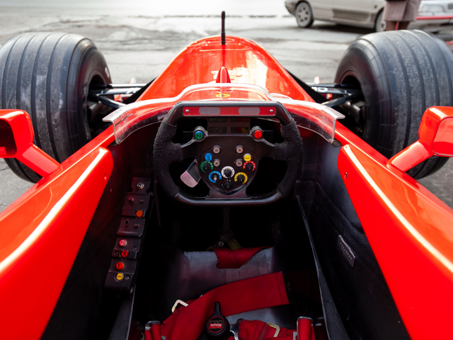 Cockpit and steering wheel view of red Ferrari racing sports cars for Formula 1 on the street near the garage box.