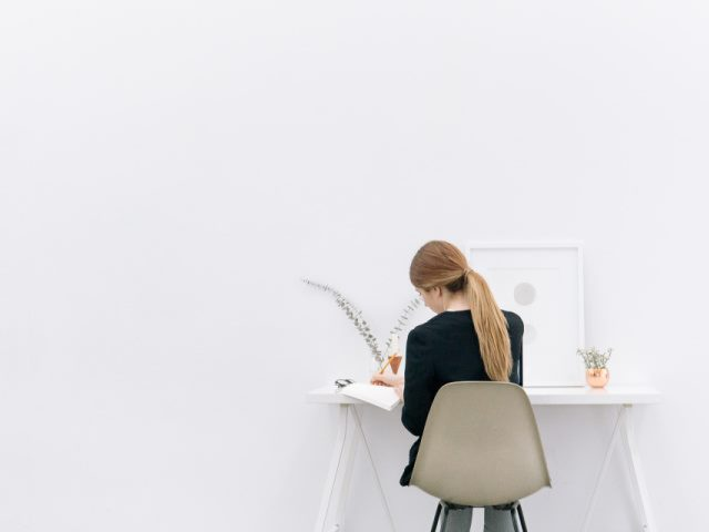 woman working alone at a desk on a large white background