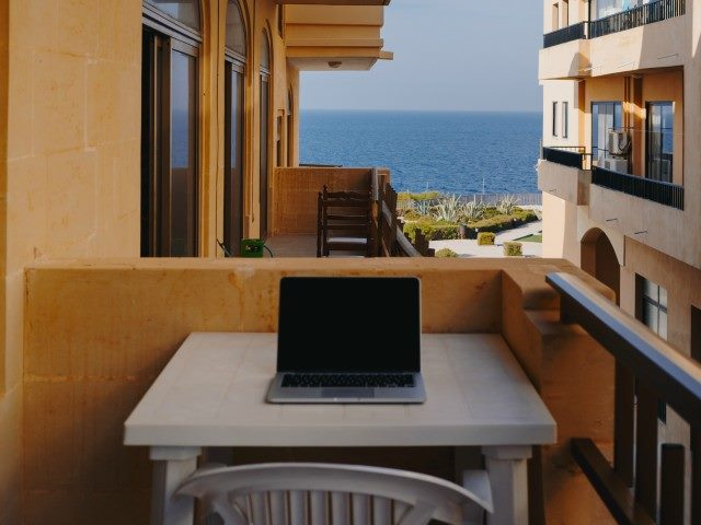 A laptop on a table on a deck between apartment buildings. Ocean view in the background.