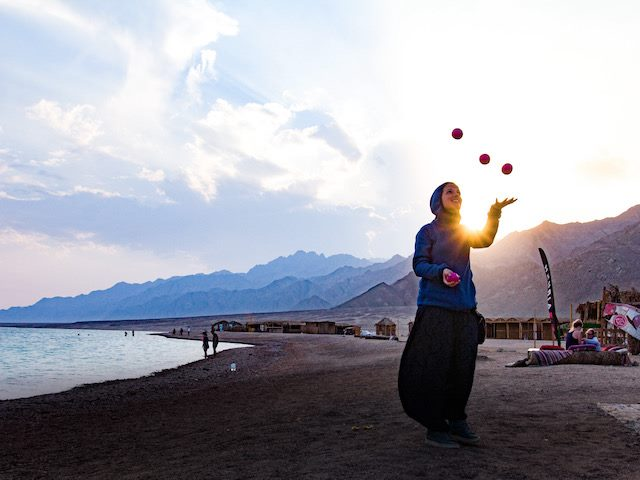 woman juggling on a beach