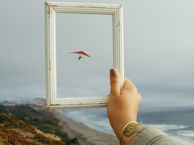 person holding a rectangular white frame while looking out in the distance