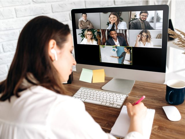 Online training. The back view of a girl who learns online by video conference online. On the screen, the teacher tells the information to her and other participants in the conference.