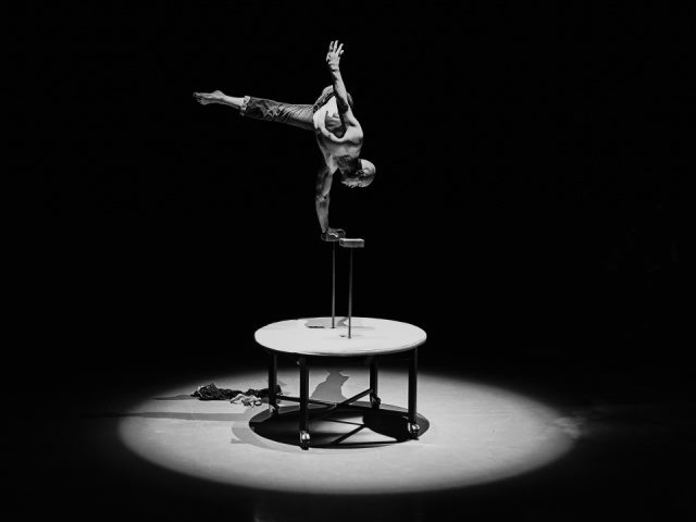 grayscale photograph of a man doing acrobatics on a round table