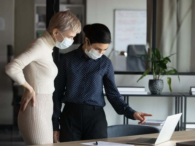 Two women wearing medical masks standing looking over a laptop screen.