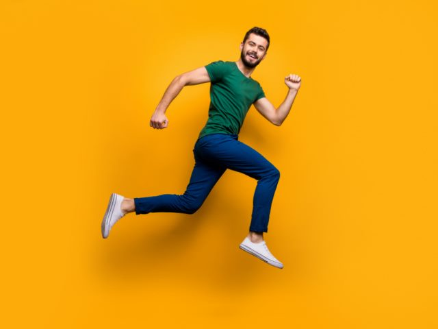 photo of cheerful man running fast in front of a yellow background