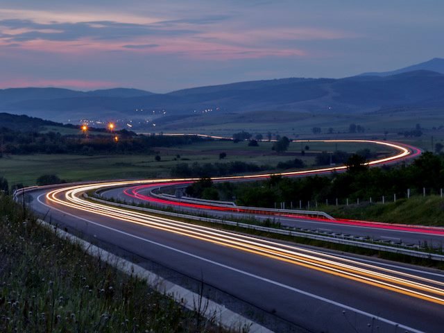 cars speeding down  a highway at dusk,  lights on