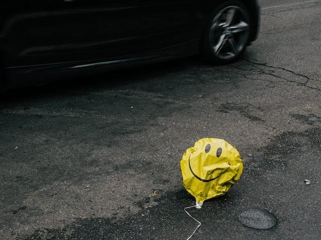 deflated smiley face balloon on the street