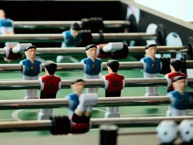 close up of foosball figures, opposing teams