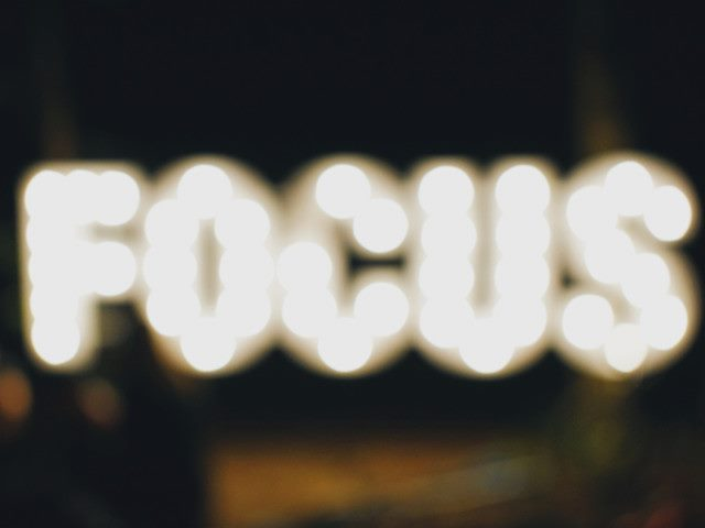 "blurry picture of a neon sign that says ""Focus"""