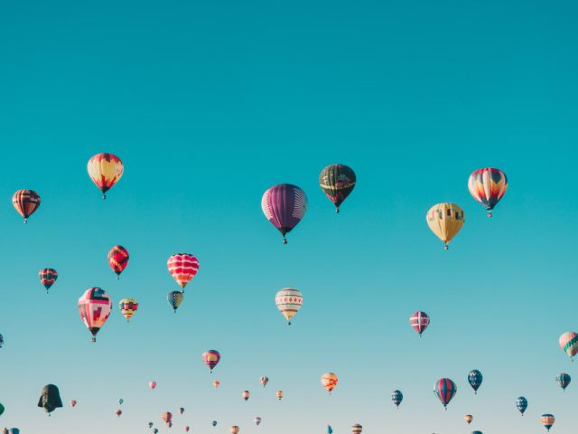 hot air balloons rise into a blue sky