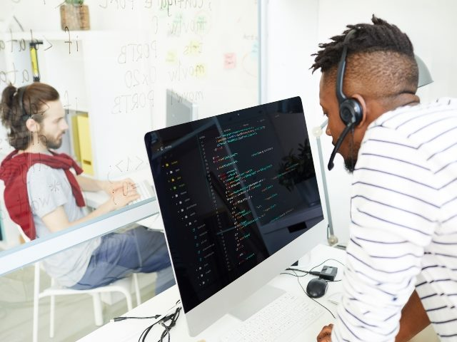 Man with a headset on looking into a computer screen as another man sits on the other side of a glass divider.