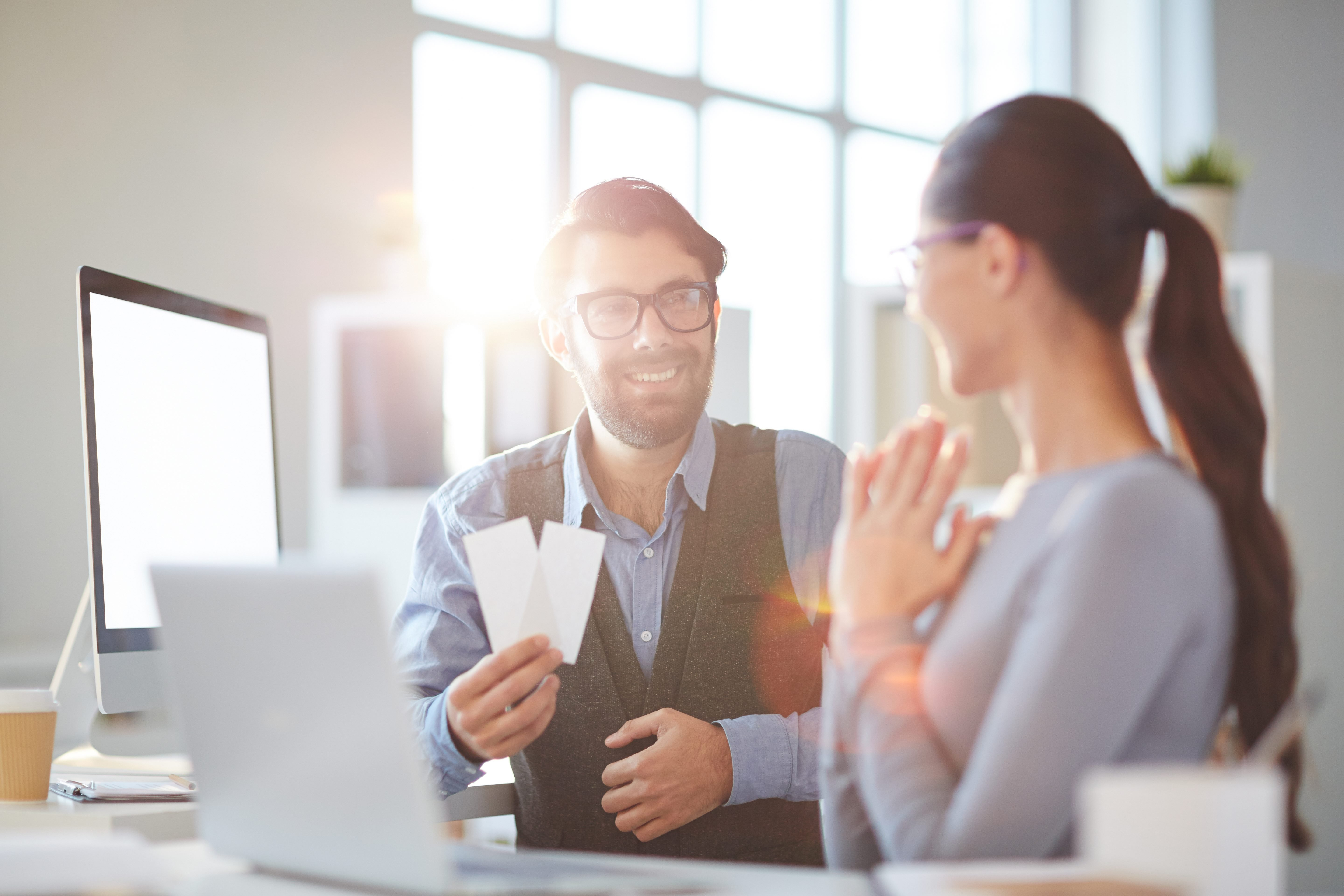 man presenting woman with tickets at work