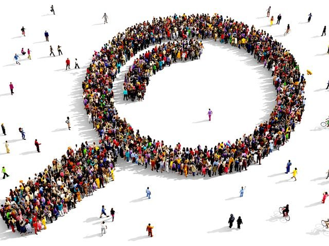 large group of people seen from above gathered together in the shape of a magnifying glass icon