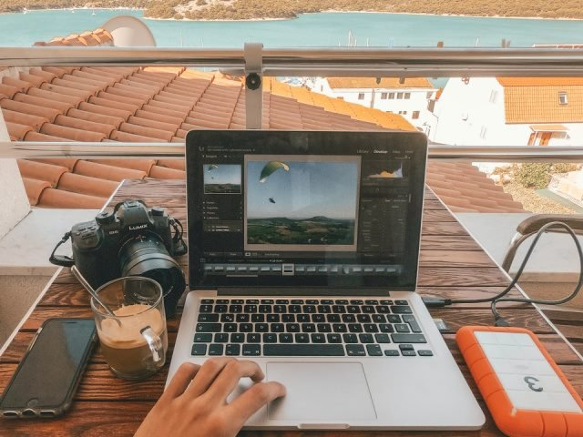 man working on a laptop computer beside an orange power bank with the ocean in the background