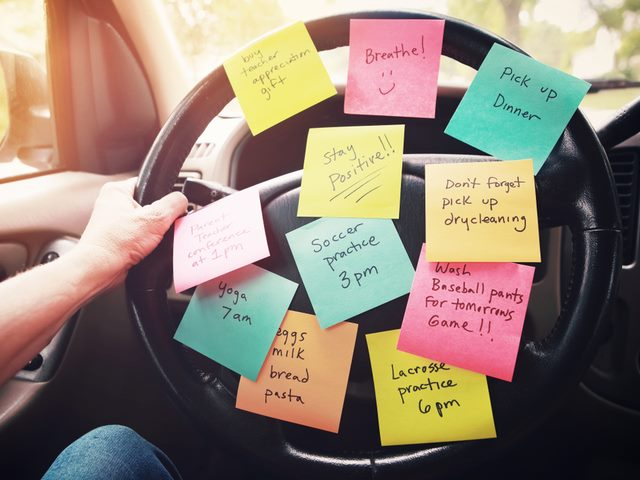 A steering wheel with post-it notes taped to it.