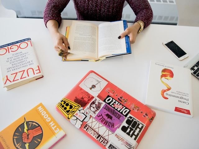 woman surrounded by a number of business related books