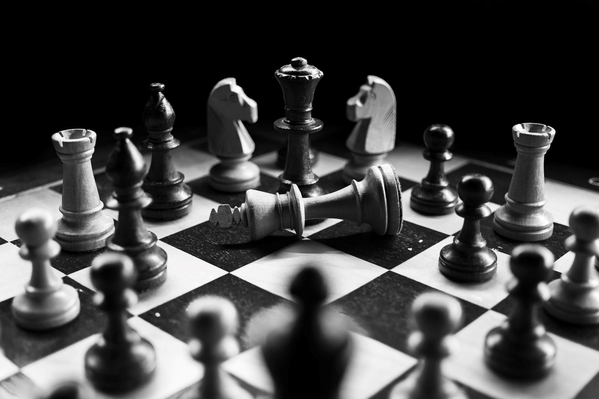 black and white chess pieces with king overturned