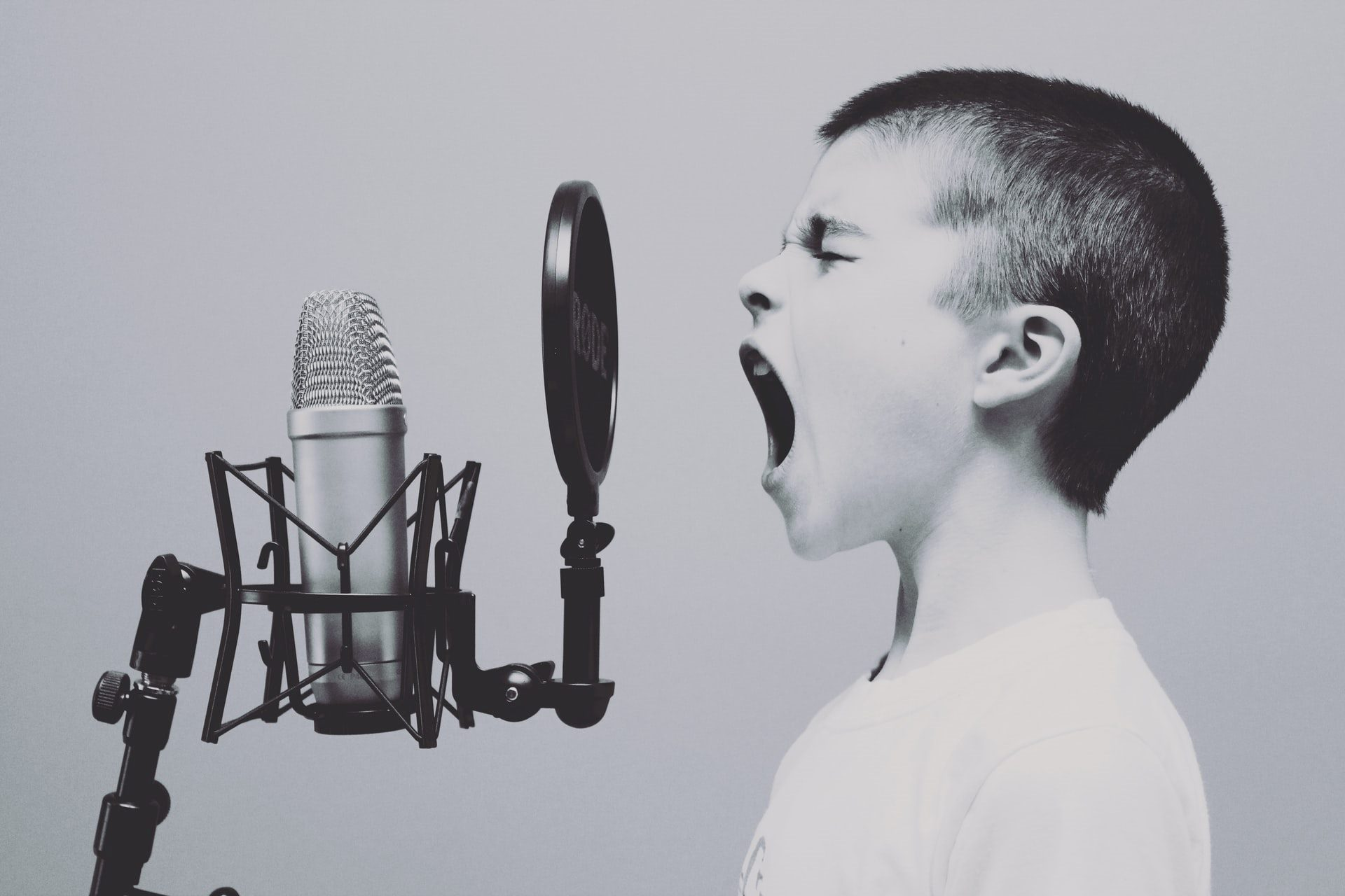 kid shouting into a microphone black and white