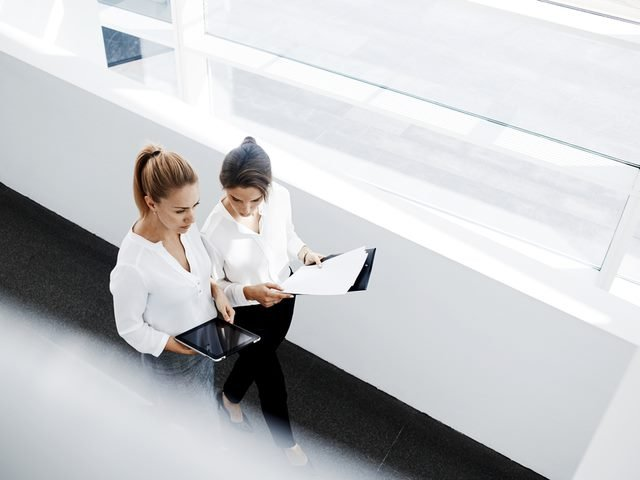 Young businesswomen, one of which is using a portable digital tablet, walk together in an office setting.