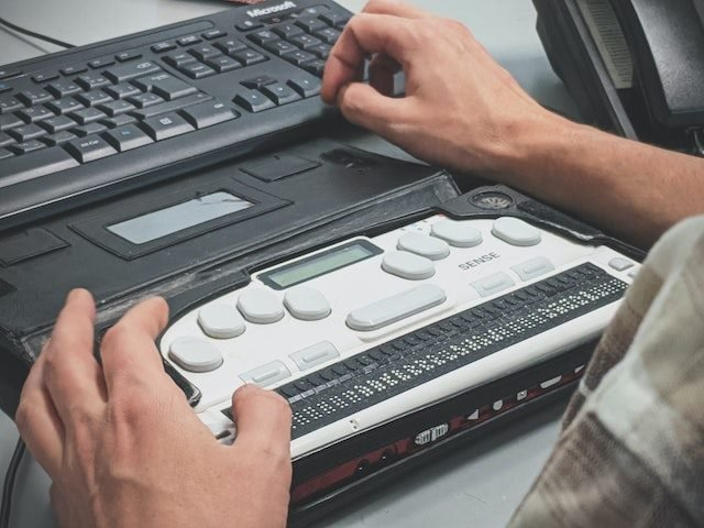 man using a braille reader keyboard with his computer