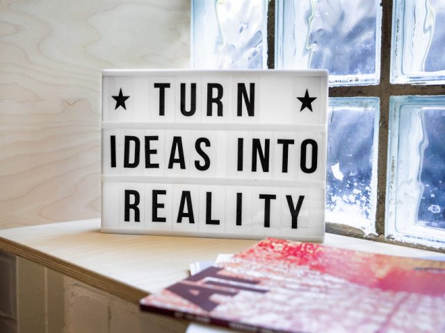 white and black sign on a shelf that says Turn Ideas Into Reality