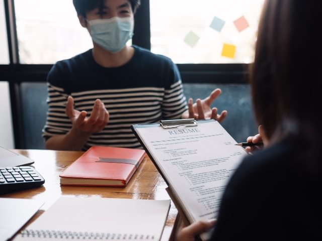 Man with a medical mask smiling as he looks across a desk at a women interviewing him for a job.