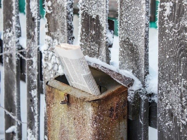 Post box with newspaper in the winter on the street.