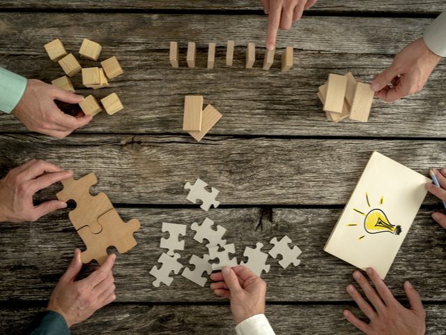 Business workers planning workplace strategy while holding puzzle pieces, creating ideas with light bulb drawn on paper and rearranging wooden blocks. - Workplace strategy
