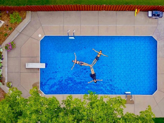 three women swimming in a pool photographed from above