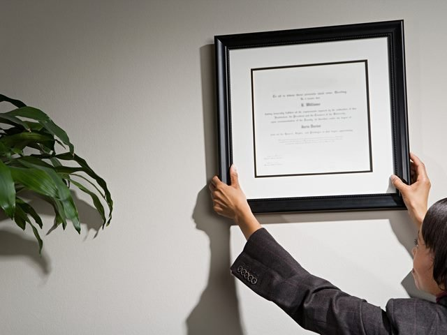 Business woman hanging framed certificate.