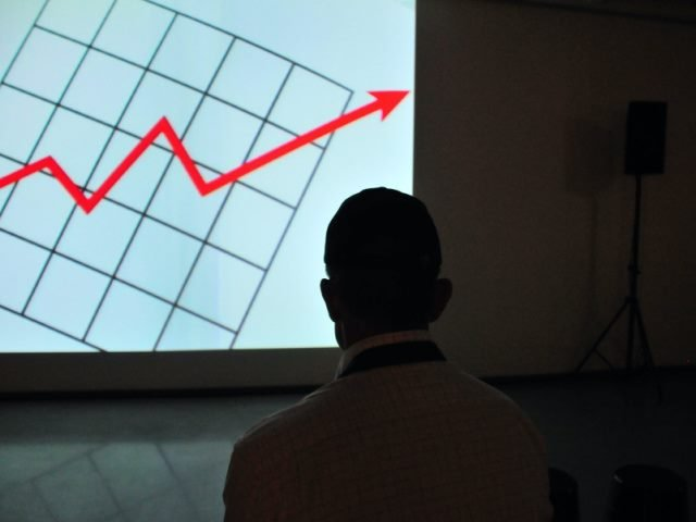 man in a white shirt looking at a graph with a red arrow pointing up
