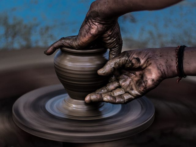 throwing a  pot on a pottery wheel
