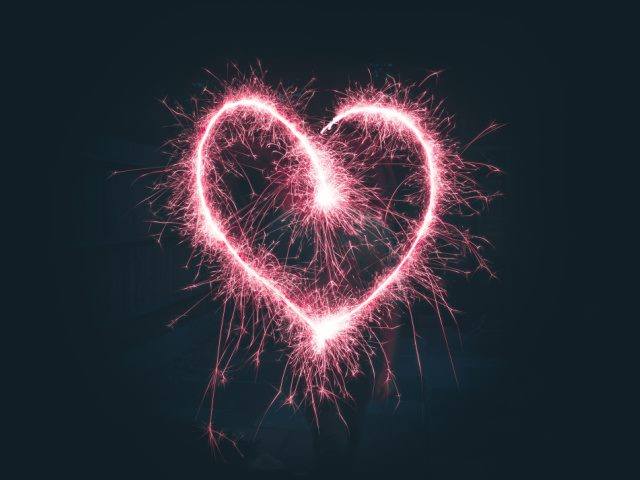 heart shaped pink sparklers on a dark background