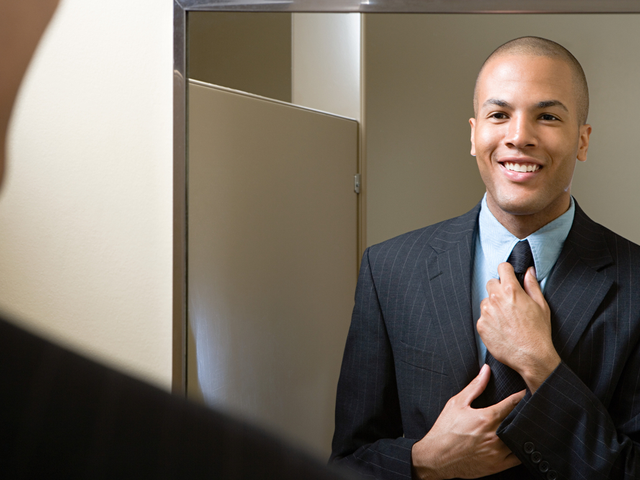 A man adjusting his tie in a mirror - new hire
