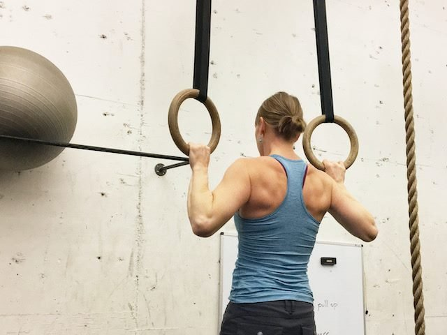 woman doing a chin up on rings at a gym