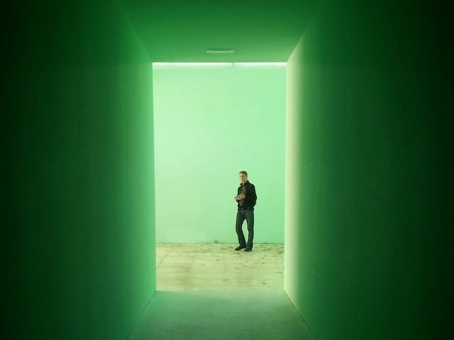 man at the end of  a  green tunnel