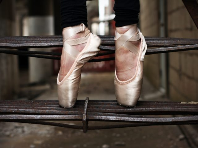 a woman holds a dance position in ballet shoes on a metal staircase