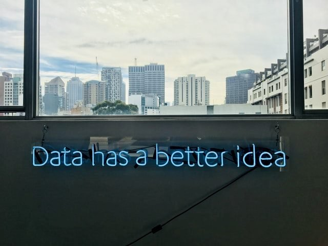 cityscape background with neon sign in foreground that says data has a better idea