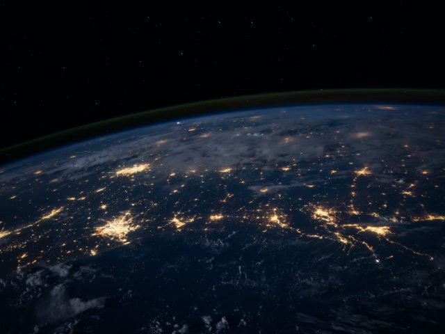 night time photo of Earth from space showing cities lit up brightly